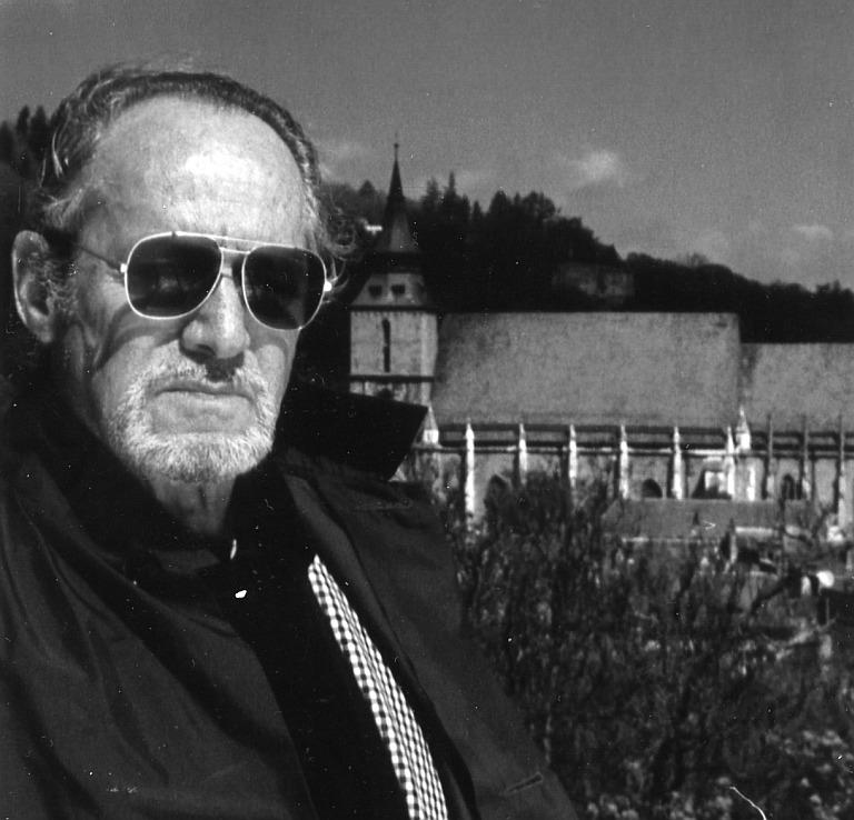 """Hans Bergel, 1995, anlässlich der Dreharbeiten für den ARD-Film """"Grenzgänger - der Schriftsteller Hans Bergel"""". Im Hintergrund die Schwarze Kirche in Kronstadt, Siebenbürgen."""